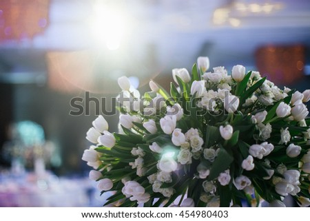 Stunning bouquet made of white tulips stands on the dinner table - stock photo