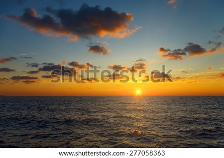 stunning bright sunset on the beach with dramatic clouds - stock photo