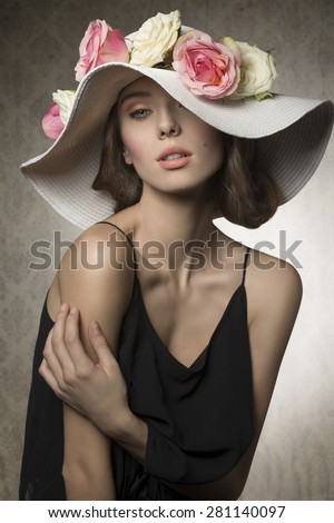 stunning brunette woman posing in summer fashion portrait with romantic big hat with colorful flowers. Wearing black dress and looking in camera with sensual expression  - stock photo
