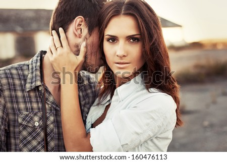 Stunning closeup portrait of young beautiful brunette in love posing with her sensual boyfriend. Pretty couple together in summer.  - stock photo