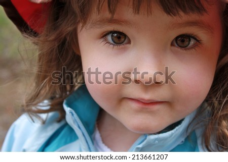 stunning closeup up of little girl with brown eyes taken outdoors - stock photo