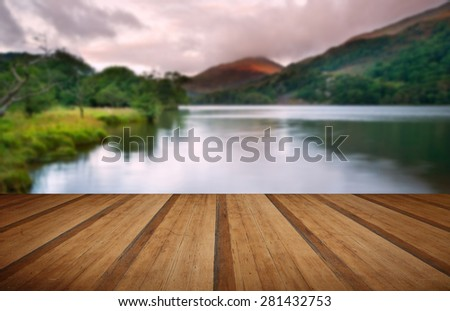 Stunning colorful sunrise over lake with mountain range in distance with wooden planks floor - stock photo