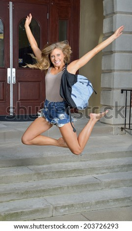 Stunning female college student jumps for joy outside of building - stock photo