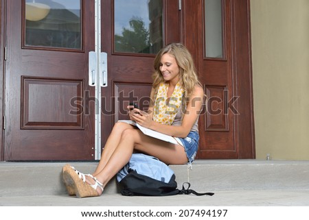 Stunning female college student sitting outside building with book on lap texting on mobile phone - back to school themed - stock photo
