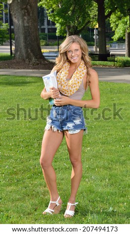 Stunning female college student stands outside with her books  - stock photo