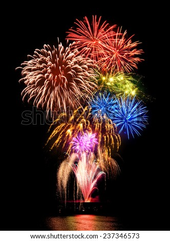 Stunning fireworks display with happy colors on black night sky background, reflected on water - stock photo