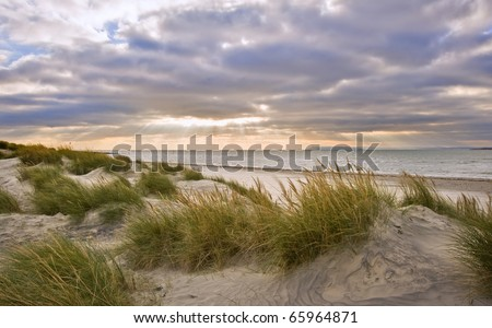 Stunning inspirational sunset image with glowing sun beams and grassy sand dunes - stock photo