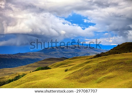 Stunning landscape - hills of savanna covered with yellow grass under stormy cloudy sky - stock photo