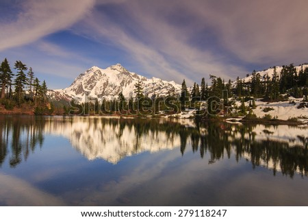 Stunning landscape of snowy mountain reflecting over the water - stock photo