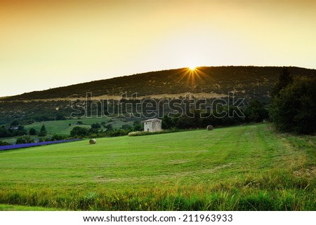 Stunning landscape with field and old farmhouse at sunset. Plateau of Sault, Provence, France - stock photo