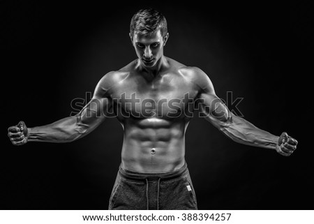 Stunning muscular man showing perfect abs, shoulders, biceps, tr - stock photo