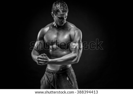 Stunning muscular man showing perfect shoulders, biceps, triceps - stock photo
