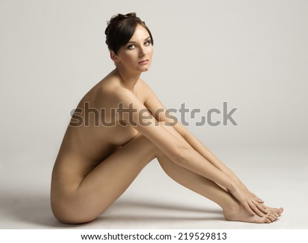 stunning naked body of a very sensual and beautiful woman in beauty pose ,looking in camera gently , natural skin - stock photo