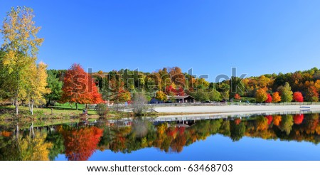 Stunning New England lake in fall with blue sky - stock photo