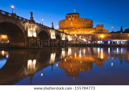 Stunning Ponte Sant'Angelo bridge crossing the river Tiber and Castel Sant'Angelo (AD 135), mausoleum of Hadrian, now a museum and art gallery illuminated at night in the heart of Rome. - stock photo