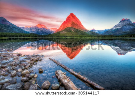 Stunning reflections on Swiftcurrent Lake in northern Montana at sunrise - stock photo