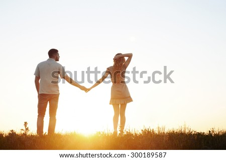 stunning sensual young couple in love posing in summer field at the sunset, happy lifestyle concept - stock photo