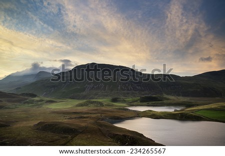 Stunning Summer sunrise over mountain range with lake and beautiful sky - stock photo