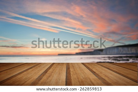 Stunning Summer sunset over ocean with cliffs, rocks and vibrant colors with wooden planks floor - stock photo