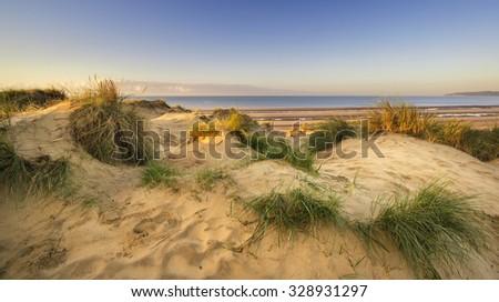 Stunning sunrise over sand dunes system on yellow sand golden beach - stock photo