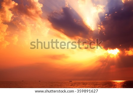 Stunning sunrise over the sea with fantastic sunbeam through the black stormy cloud.  - stock photo
