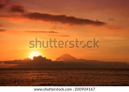 Stunning Sunset of Vibrant Colors on a Seaside with Volcano on a background - stock photo