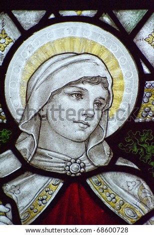 Stunning 15th Century stained glass window detail with vibrant colors and excellent detail of Faith - stock photo