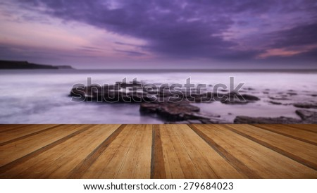 Stunning toned landscape seascape coastline and rocky shore at sunset with wooden planks floor - stock photo