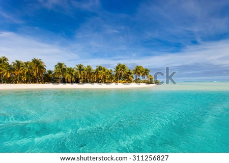Stunning tropical island with palm trees, white sand, turquoise ocean water and blue sky at Cook Islands, South Pacific - stock photo