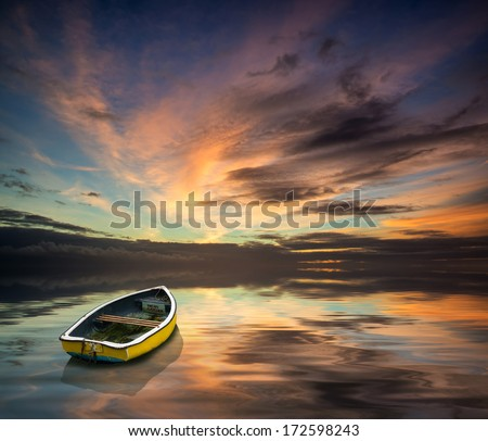 Stunning vibrant blue and pink Winter sky with single boat floating on ocean - stock photo