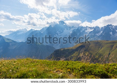 Stunning view of Mont Blanc massif (4810 m) and his melting glaciers. Summer adventures in the Italian French Alps. Shot in backlight with scenic clouds covering the sun and meadows in the foreground. - stock photo