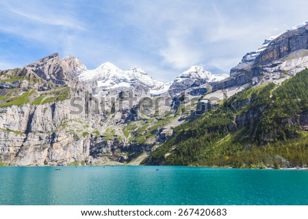 Stunning view of Oeschinensee (Oeschinen lake) with Bluemlisalp and Frundenhorn of swiss alps on Bernese Oberland. Photo taken in summer on the hiking path at the lake side, Switzerland - stock photo