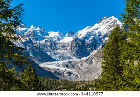 Stunning view of the Bernina massive and Morteratsch glacier on the hiking path in the forest in Engadine area of Switzerland. - stock photo