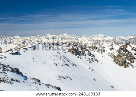 Stunning view of the faraway high peaks of the Ecrins Massif National Park, France, arising from the alpine arc in late winter season and beginning of spring. Wide angle shot from Italy France border. - stock photo