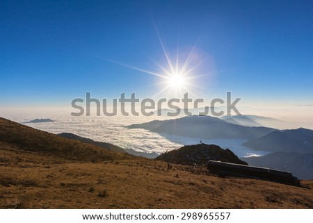 Stunning view of the sunrise with silhouette of mountains and magnificent cloudscape on top of Cattle Back Mountain (Niubeishan) in Sichuan Province, China - stock photo