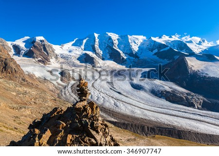 Stunning view stone heap at the mountain Munt Pers with the Bernina massive including Piz Palu and Morteratsch glacier  in the background, near Diavolezza in Engadine, Switzerland. Selective focus. - stock photo
