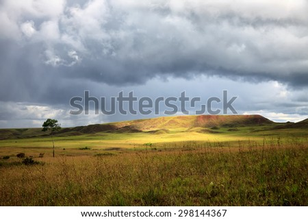 Stunning view to savanna under stormy cloudy sky with single bright patch of sunlight  - stock photo