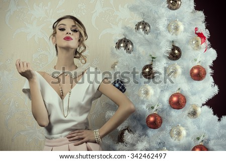 stunning woman with aristocratic fashion style and pose near decorated christmas tree with elegant clothes, precious pearl necklace and stylish make-up  - stock photo