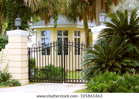 Stunning yellow mansion protected in a gated community - stock photo