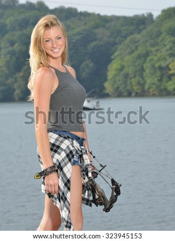 Stunning young blonde woman archer stands in front of lake holding her compound bow - flannel shirt tied off around her waist - stock photo