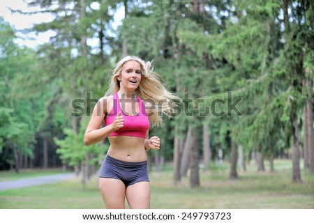 Stunning young blonde woman jogging outdoors in a pink sports bra and gray shorts  - stock photo