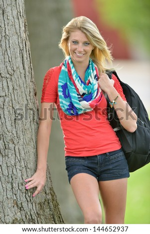 Stunning young blonde woman leaning against a tree with her backpack on a college campus - student or education stock - stock photo