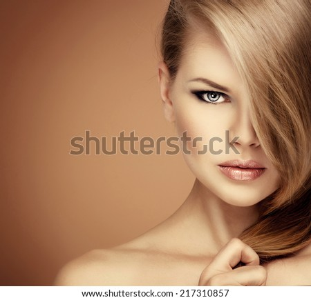 Stunning young Caucasian blond model showing her shiny long straight hair.  - stock photo
