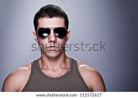 Stunning young man, with a very serious expression, appealing as the bad guy. The man is wearing sun glasses and some of his muscles are visible. A dramatic lighting has been used. - stock photo