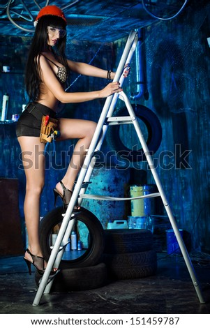 Stunningly sexy girl posing with tools in the old garage.  - stock photo