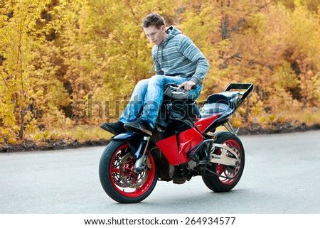 Stunt rider is riding motorbike without feet - stock photo