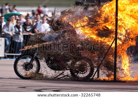 Stunt rider riding through a wall of flames - stock photo