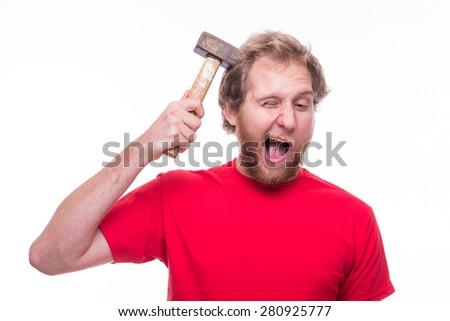 Stupid man strikes his head with a hammer - studio shoot  - stock photo