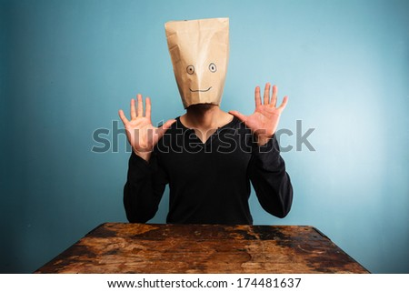 Stupid man with bag over his head and hands up - stock photo
