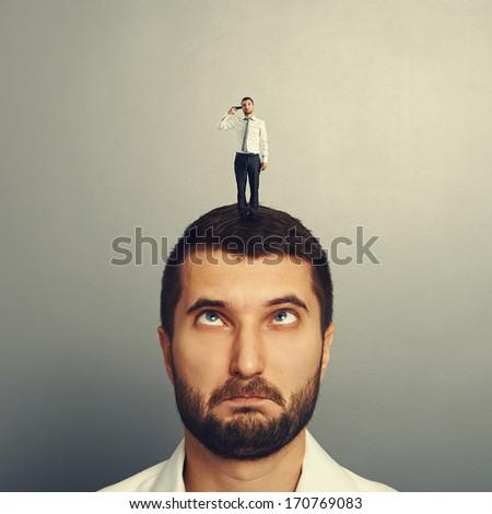 stupid man with small hopeless man on the head - stock photo
